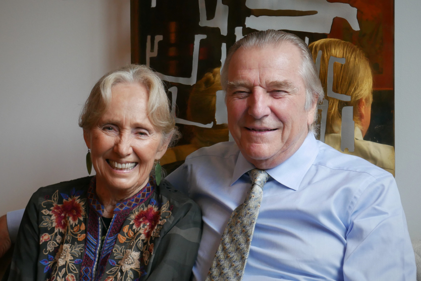 Dr Lola Van Wagenen and Dr George Burrill sitting on a couch, smiling.