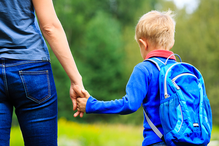 Generic photo of a child with a schoolbag holding his mother's hand, shot from behind with faces not visible.