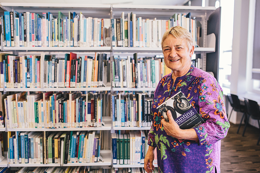 Marilyn Waring standing in a library.