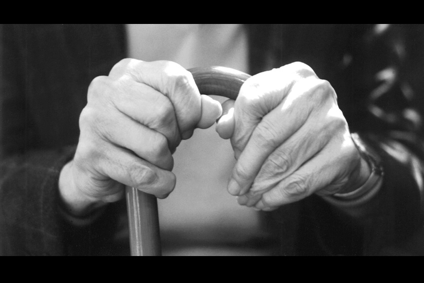 An old person's hands with a walking stick