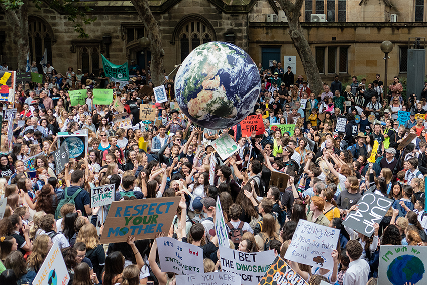 A climate protest march with protesters hold up a giant globe.