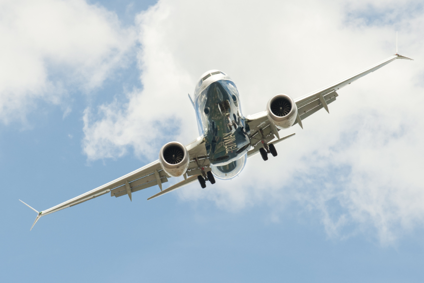 A Boeing 737 MAX in the air, seen from the front.