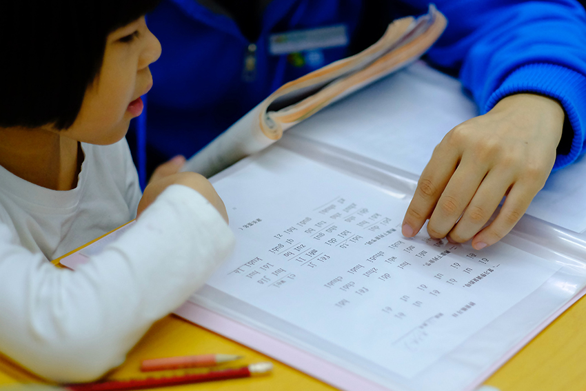 A child being studying with a parent.