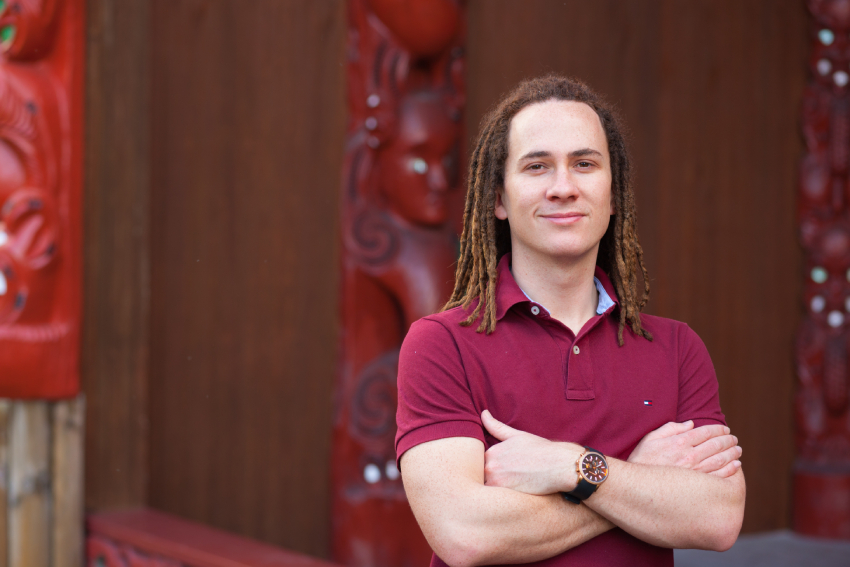 AUT Lecturer Hēmi Kelly standing arms crossed in front of the AUT marae.