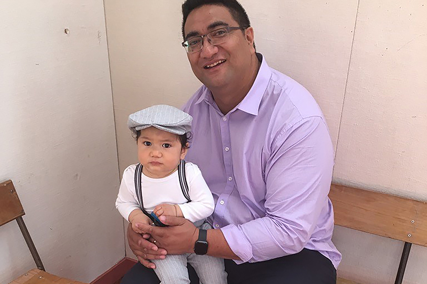 Associate Professor El-Shadan Tautolo with his child on his knee.