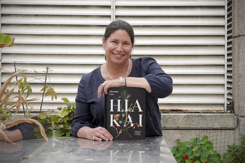 Tracy Berno holding the book Hiakai and smiling.