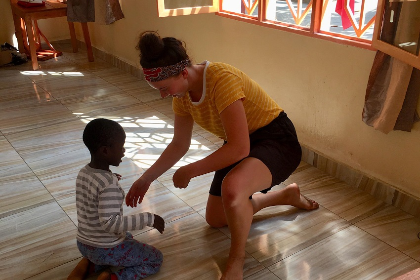 Eloise Wilson helping a child in Burundi