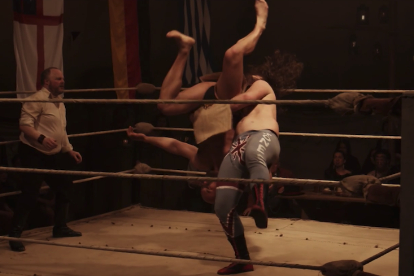 Screenshot of TVNZ's Colonial Combat showing two wrestlers in the ring and referee.