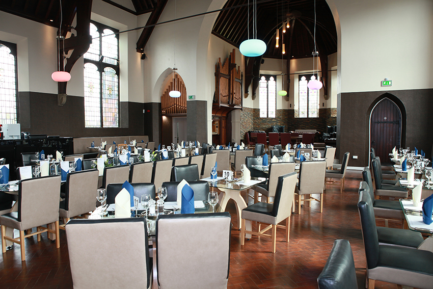 Chairs and tables laid out for fine dining in a The Clink restaurant.