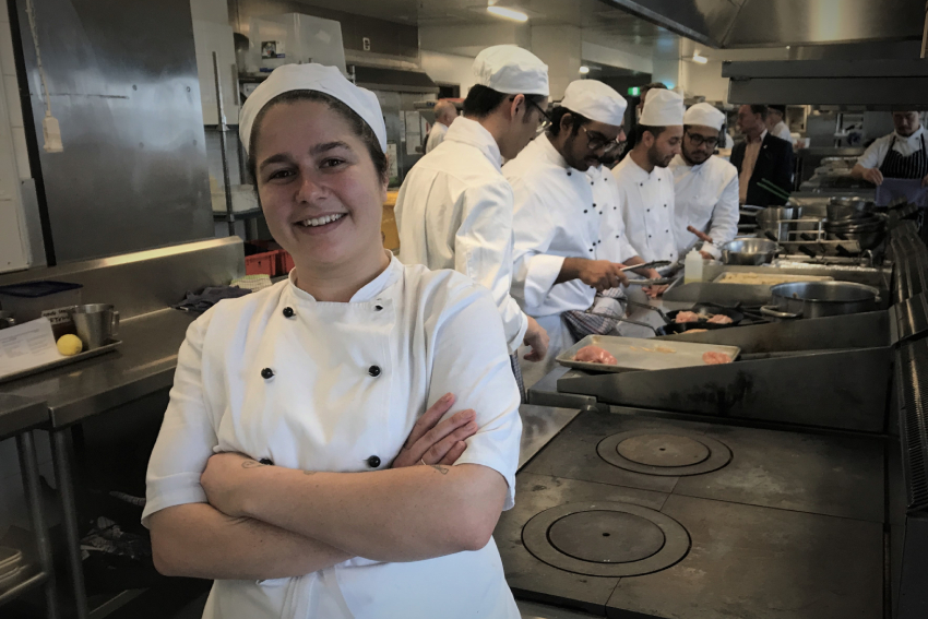 Hospitality student Sally Claire Nutt smiling in the foreground, with four of her fellow students preparing food behind.