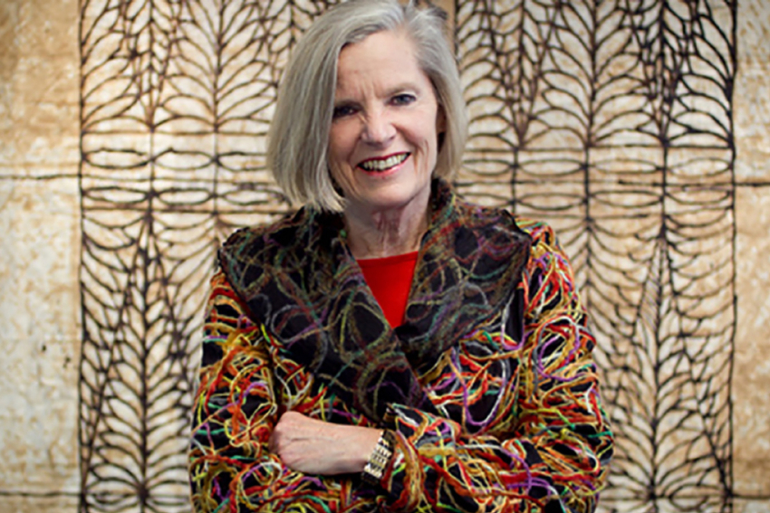 Professor Judy McGregor, smiling and standing in front of a Pacific Island artwork.