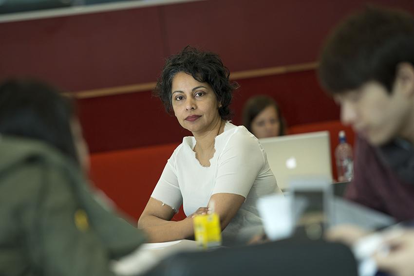 Professor Rhema Vaithianathan sitting arms crossed and looking at the camera.